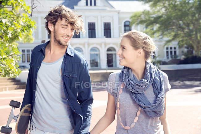 Улыбающаяся молодая пара на улице — стоковое фото