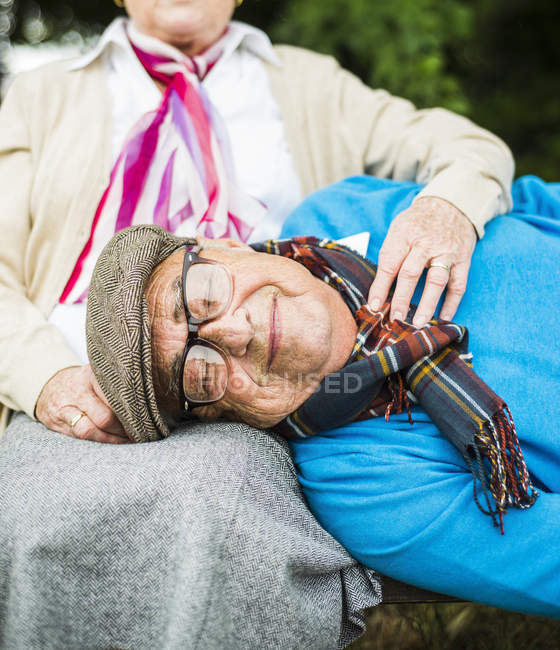 Portrait of senior man lying with head on his wife's lap — Stock Photo