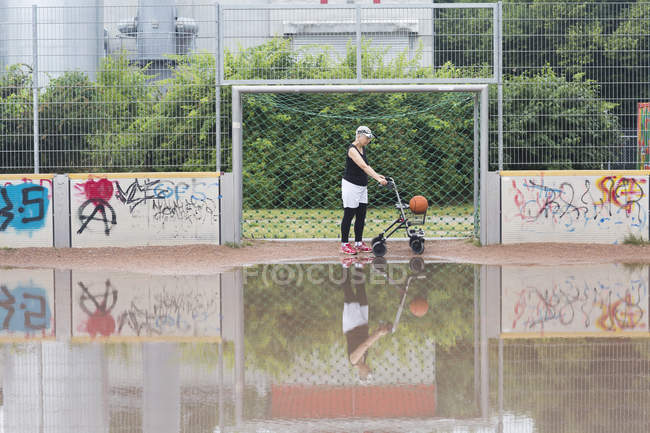 Senior woman with wheeled walker on sports ground — Stock Photo