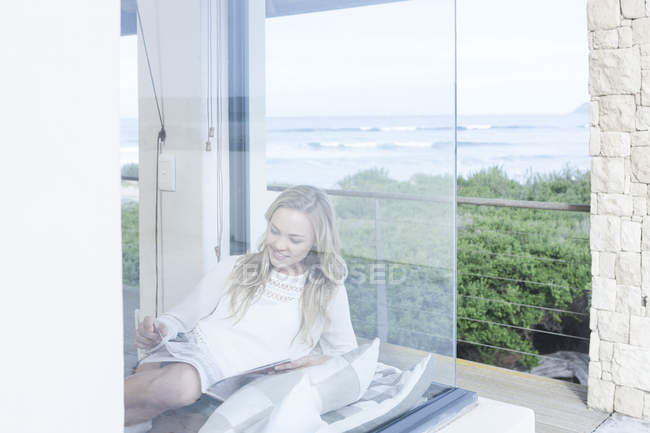 Молода жінка читання журналу в будинку пляж — стокове фото