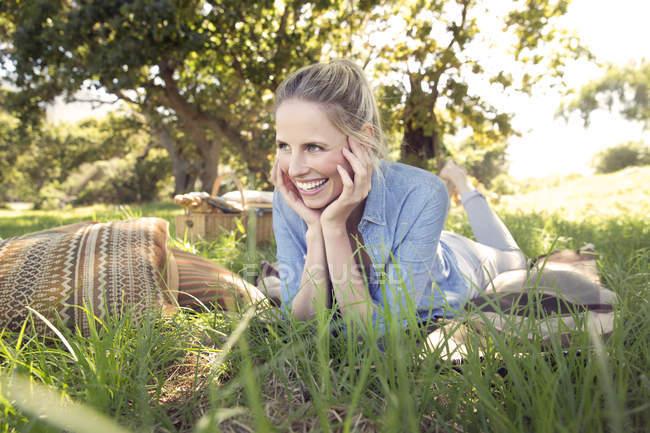 Donna felice sdraiata sul prato — Foto stock