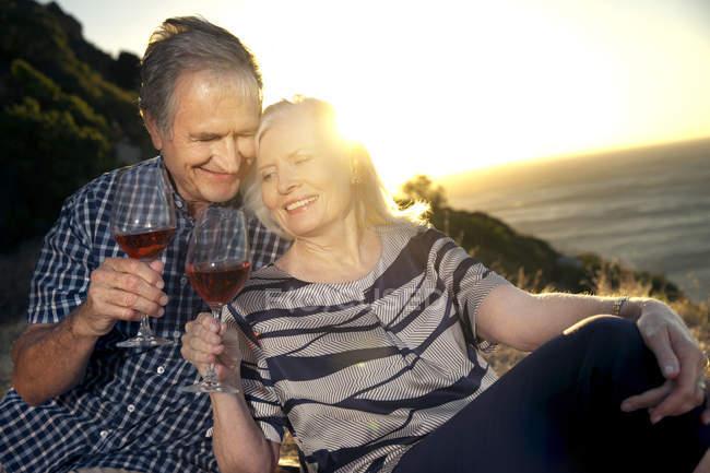 Happy senior couple with glasses of red wine — Stock Photo