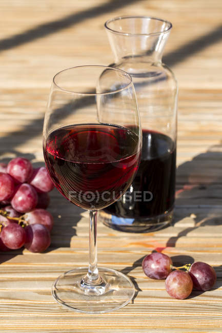 Glass and carafe with red wine and red grapes at wooden table — Stock Photo