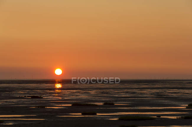 Alemanha, Lower saxony, Dorum, pôr do sol sobre a água do mar — Fotografia de Stock