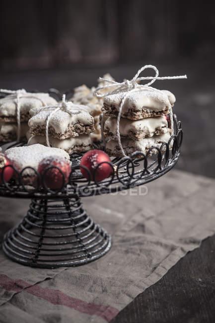 Con azúcar en polvo rociada rojo adornos de Navidad en el soporte de la torta y galletas de canela en forma de estrella - foto de stock