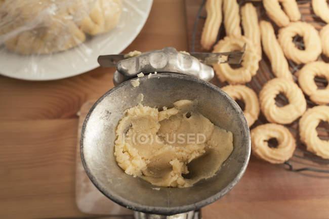 Preparación spritz cookies y masa cruda en metal máquina de picar carne, vista elevada - foto de stock