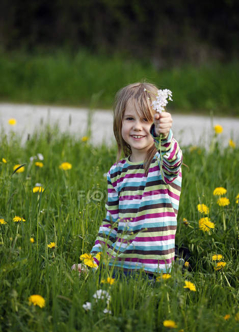 Girl sitting in meadow and showing wildflowers — Stock Photo