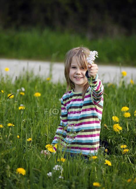 Fille assise dans la prairie et montrant des fleurs sauvages — Photo de stock