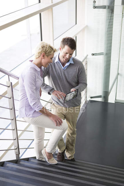 Business people using digital tablet, smiling — Stock Photo