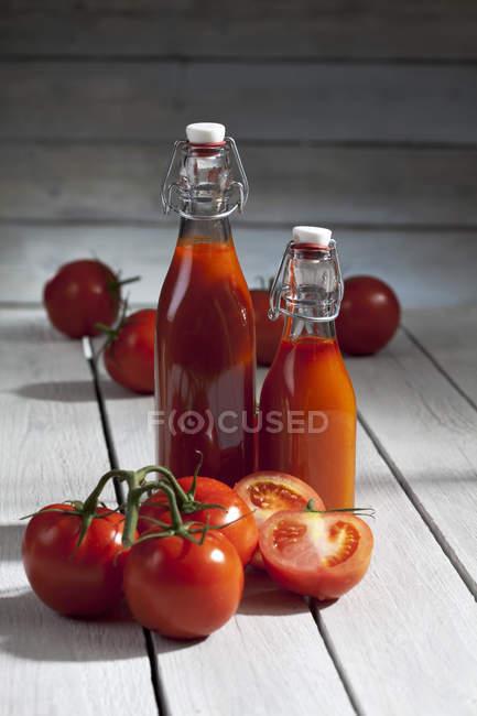 Gros plan de deux bouteilles de jus de tomate maison avec des tomates fraîches sur la table en bois — Photo de stock