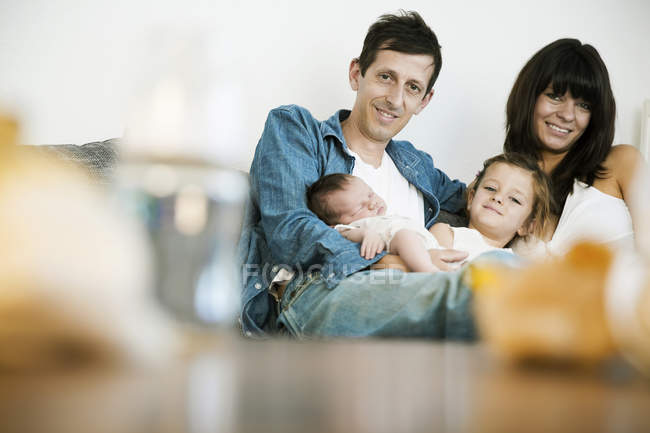 Young family with male newborn and little daughter sitting on sofa at home — Stock Photo