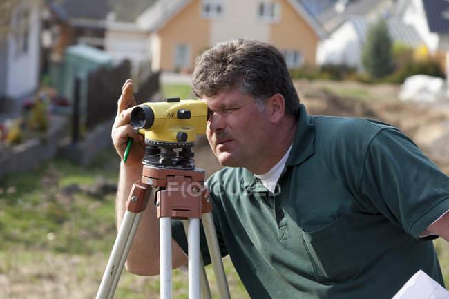Operaio manuale che effettua la misurazione laser in cantiere — Foto stock