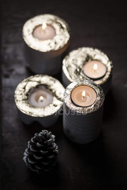 Elevated view of four lighted advent candles and fir cone placed on dark wooden table — Stock Photo
