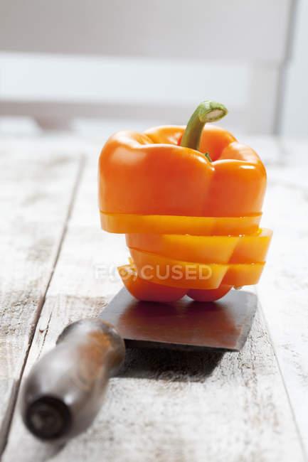 Sliced orange sweet pepper stacked on chopping knife — Stock Photo