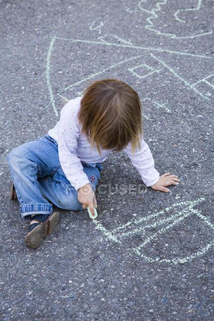 Маленька дівчинка малюнок олівцем на асфальті — стокове фото