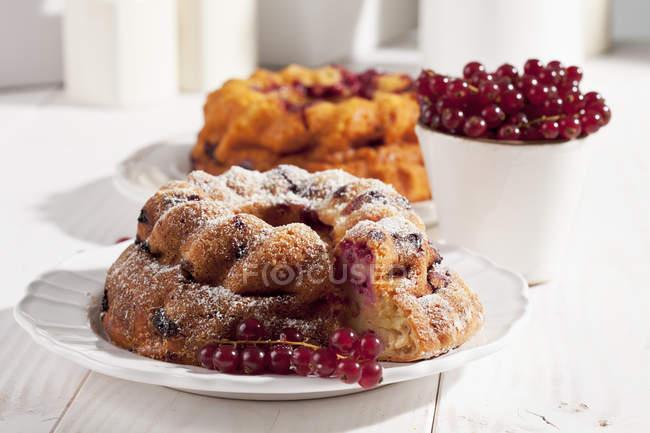 Чизкейк из красной смородины с сахарной пудрой и чаша красная смородина на белый деревянный стол — стоковое фото