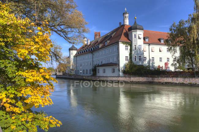 Германия, Бавария, Ландсхут, Хайлиг-Гейст-Шпиталь над водой — стоковое фото