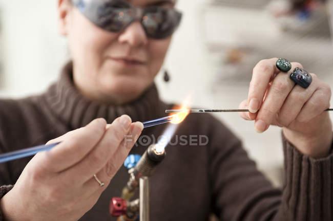 Mature woman making glass beads — Stock Photo