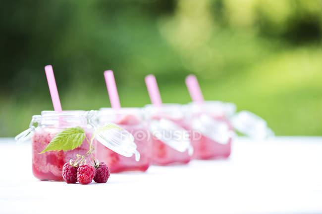 Close-up di frullato di lampone in vetro vasetti con cannucce — Foto stock