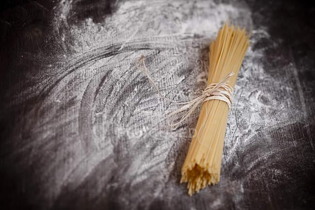 Spaghetti auf Holztisch mit Mehl — Stockfoto