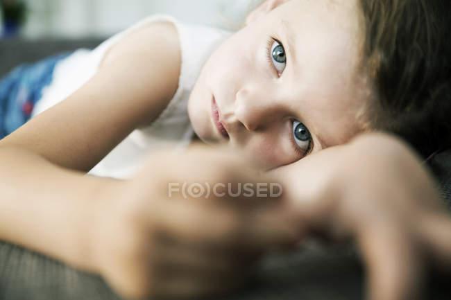 Грустная маленькая девочка лежит на диване, крупным планом — стоковое фото