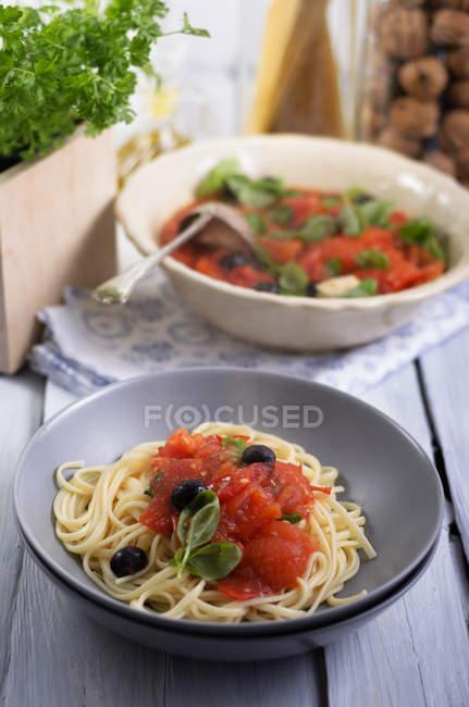Espaguetis con salsa de tomates a la parrilla con aceitunas negras y hojas de albahaca, plano de estudio - foto de stock
