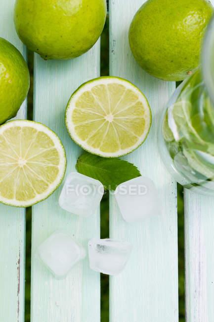 Приготування соку лайма з м'ятою, на білій поверхні дерев'яні — стокове фото
