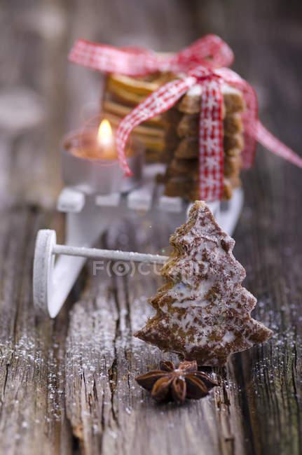 Pan de jengibre con trineo miniatura, estrellas de canela y velas - foto de stock