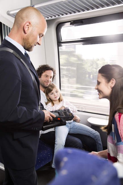 Conductor checking tickets of family in train — Stock Photo