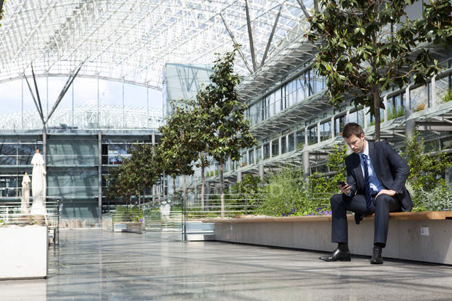 Businessman with cell phone in courtyard — Stock Photo