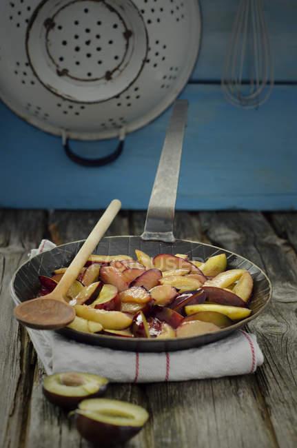Карамелізований чорнослив в сковороду з дерев'яною ложкою і серветку на дерев'яним столом, крупним планом — стокове фото