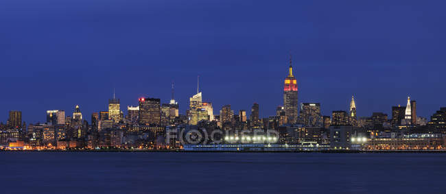 Estados Unidos, Estado de Nueva York, Ciudad de Nueva York, Vista del Bajo Manhattan iluminada por la noche con el río Hudson - foto de stock