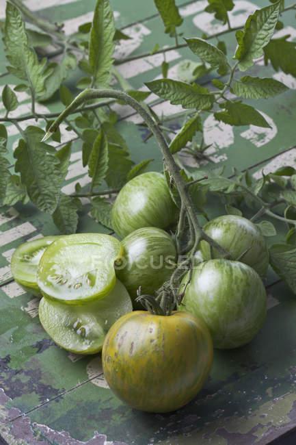 Помидоры нарезанные и весь зеленый Зебра на потертом дерево с листьями — стоковое фото