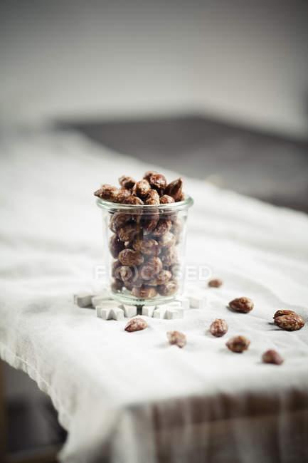 Vorderansicht des Glas von kandierten Mandeln platziert auf weißen Untersetzer in Form von Schneeflocke — Stockfoto
