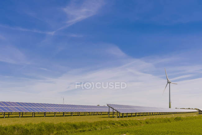Germany, Schleswig-Holstein, View of solar panel and wind turbine in field — Stock Photo
