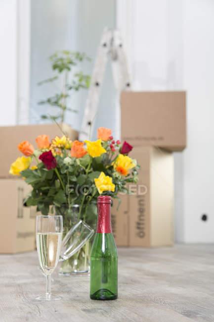Картонні коробки, шампанське та букет квітів у новому будинку — стокове фото