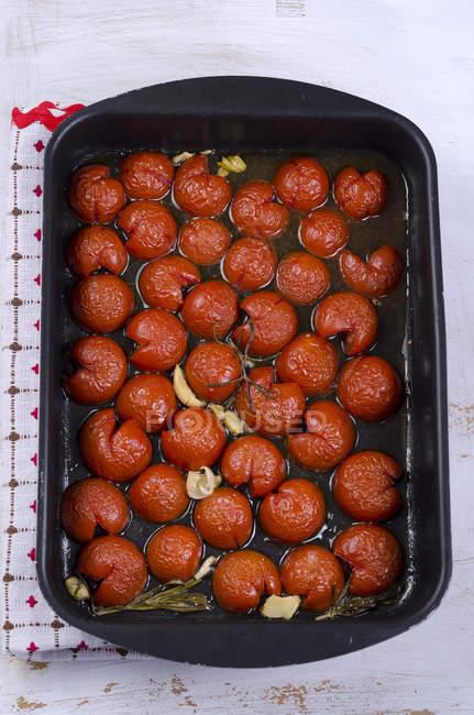 Жареные помидоры в подносе для выпечки со специями и маслом — стоковое фото