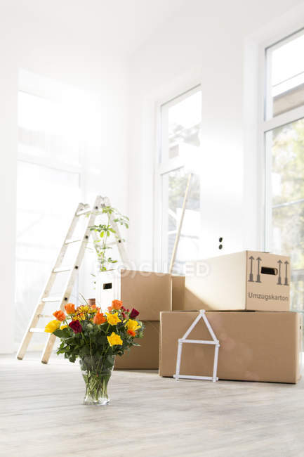 Cardboard boxes and bunch of flowers in new home — Stock Photo