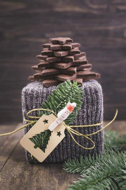 Weihnachtsgeschenk in Gestricktem Geschenkpapier mit Weihnachtsbaum aus Schokoladenzuckerkeksen und Anhänger auf dunklem Holz — Stockfoto