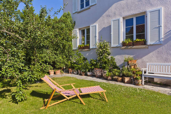 Espreguiçadeira no jardim em frente à casa — Fotografia de Stock