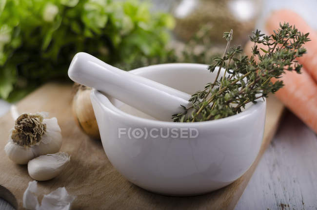 Thyme in mortar over wooden desk , close up — Stock Photo