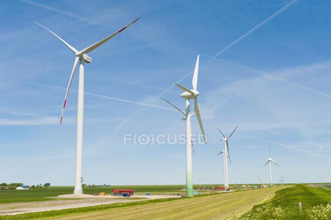 Alemanha, Schleswig-Holstein, Vista da turbina eólica em campos sobre grama — Fotografia de Stock