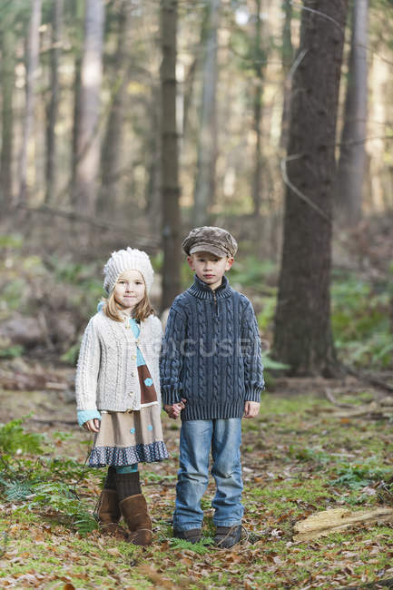 Brother and sister standing in woods holding hands — Stock Photo