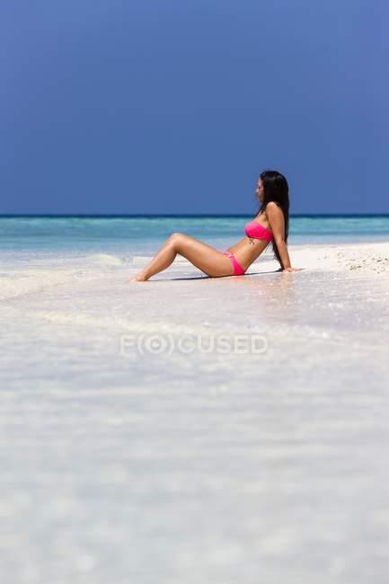 Maldive, giovane donna in bikini che si siede in acque poco profonde — Foto stock
