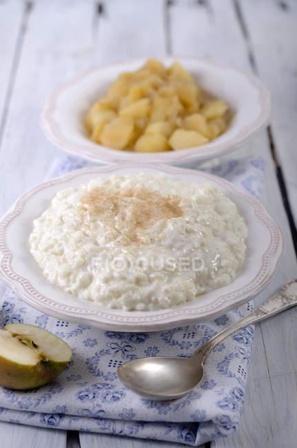 Рисовый пудинг молока в тарелку с корицей и яблочный компот на деревянный стол — стоковое фото