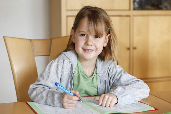Portrait of smiling girl doing homework at desk — Stock Photo