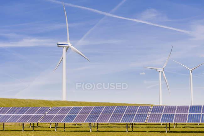 Германия, Шлезвиг-Гольштейн, просмотр панели солнечных батарей и ветряных турбин в поле — стоковое фото