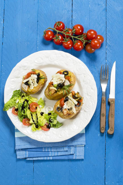 Patatas al horno mediterráneas con tomates, cebolletas, aceitunas, pollo, ricotta y queso parmesano - foto de stock