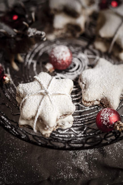 Sprinkled star-shaped cinnamon cookies with red Christmas baubles on cake stand — Stock Photo
