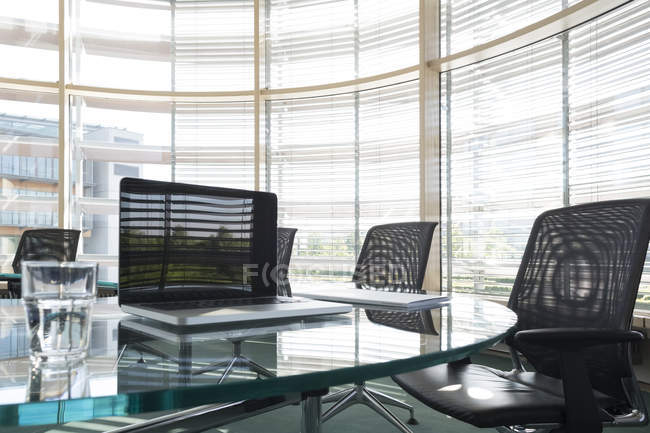 Laptop and water glass on conference table — Stock Photo